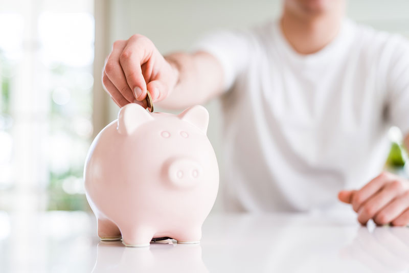 Photo of man putting money in piggy bank